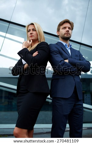 Two experienced and confident businesspeople crossing their arms while standing near office,business colleagues standing with their arms folded back to back looking into the distance, teamwork concept - stock photo