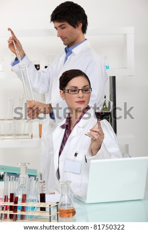 two experts analyzing wine in a laboratory - stock photo