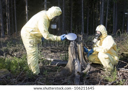 Two experts checking forest for radiation - stock photo