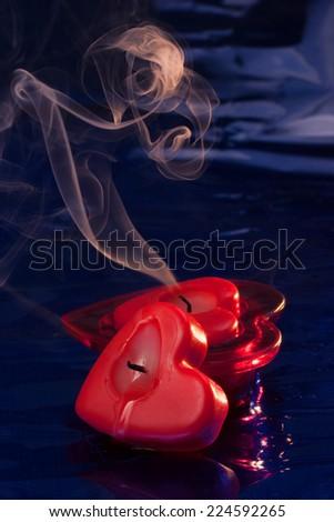 Two extinguishing heart shaped candles   - stock photo