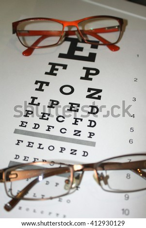 two eyeglasses and eye chart close-up on a light background - stock photo