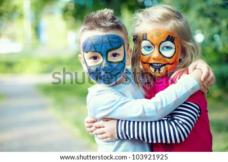 two face painted little friends embracing outside - stock photo