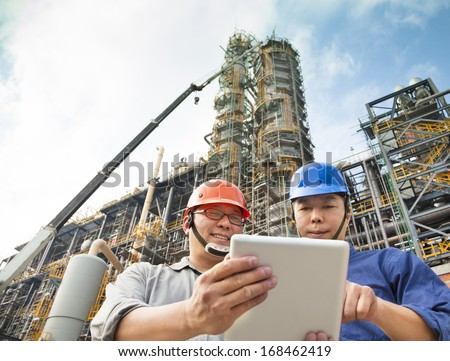 two Factory workers discussion with tablet pc - stock photo