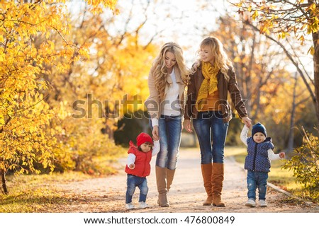 two families in autumn park. happy families having fun in fall. Smiling parents and kids family walking together outdoor in yellow fall or autumn park. Smiling young family