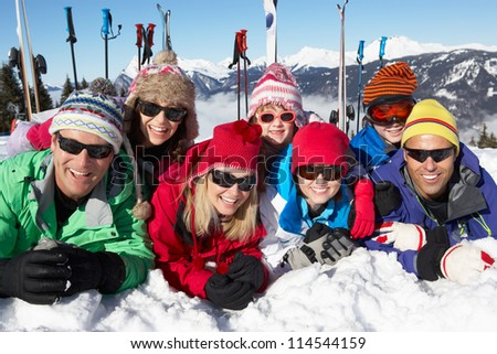Two Family Having Fun On Ski Holiday In Mountains