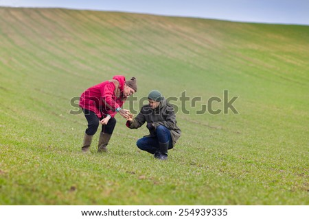 Two farmers monitoring seedlings in the field in winter time - stock photo