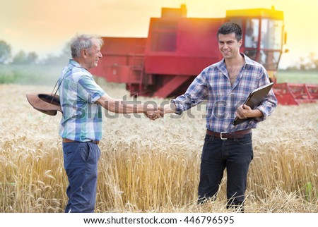 Two farmers shaking hands on wheat field while combine harvesting behind - stock photo