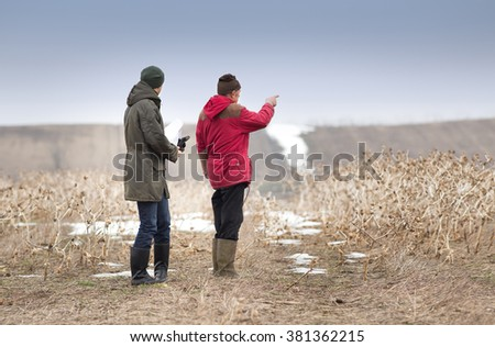 Two farmers standing on field in winter time - stock photo