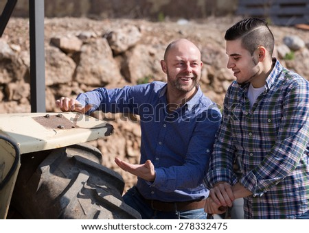 Two farmers talking near the agricultural machinery at shed  - stock photo