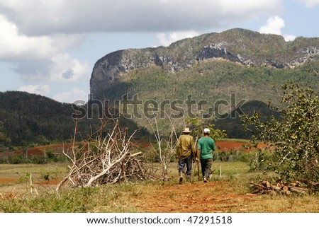 Two farmers walking in a Vinales countryside in Cuba. Most Cubans live way below established poverty lines, the  issue is biggest in rural areas - stock photo