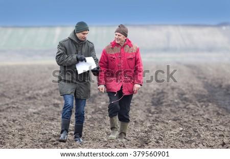 Two farmers walking on plowed field in winter time - stock photo