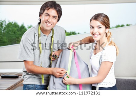 Two fashion designers taking measurement on tailoring mannequin. - stock photo