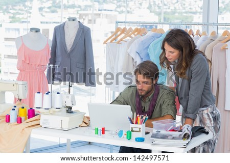 Two fashion designers working on laptop in creative office - stock photo