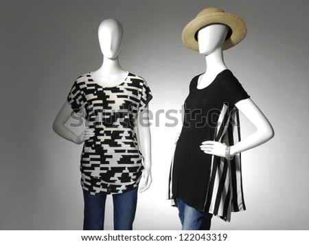 Two Fashion female clothing in hat on mannequin in light background - stock photo