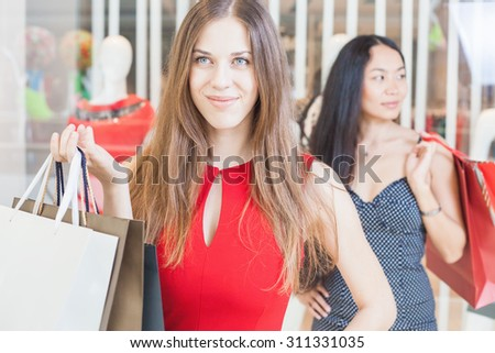 Two fashion girlfriends shopping at mall. At foreground girl looking at camera and smiling, she hold handbag at hands. At background asian woman with packages in hands. Against the boutique