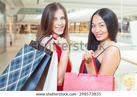 Two fashion girlfriends shopping at mall. They are looking at camera and smiling and hold handbag or bags at hands. Against the boutique