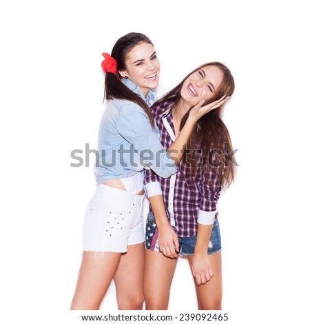 Two fashion girls having fun. Young woman closes ears girlfriend. White background, not isolated - stock photo