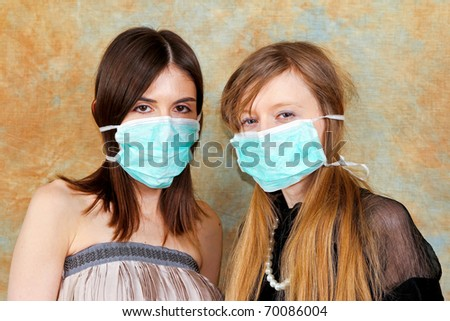 Two fashion girls with protective medical masks - stock photo