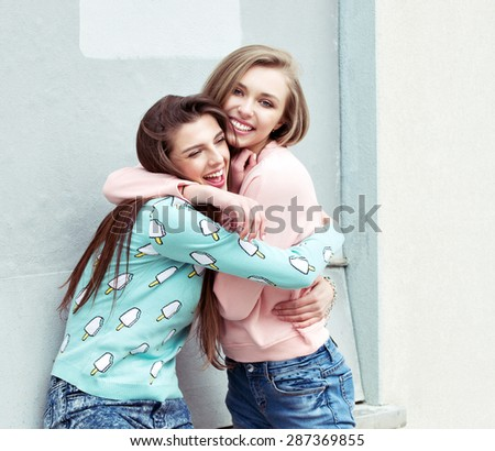 two fashion hipster girlfriends are hugging and having fun - stock photo