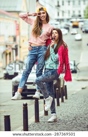 two fashion hipster girlfriends are hugging and having fun in city grunge background - stock photo