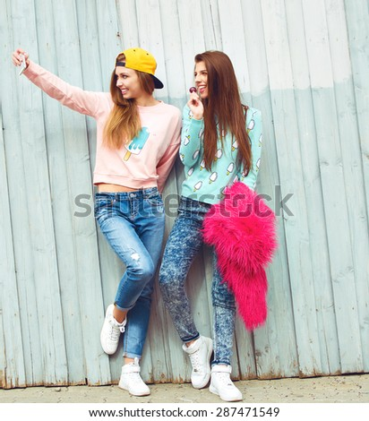 two fashion hipster girlfriends doing photo and having fun in city grunge background  - stock photo