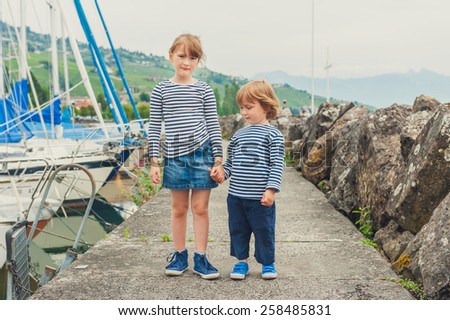 Two fashion kids, little girl and boy wearing frocks, holding hands, playing in port - stock photo