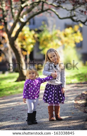 Two fashion little girl in beautiful garden - stock photo