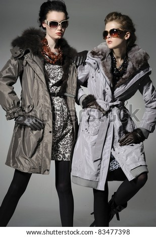 Two fashion model in autumn/winter clothes wearing sunglasses posing gray background - stock photo