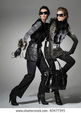 Two fashion model wearing sunglasses holding purse posing - stock photo