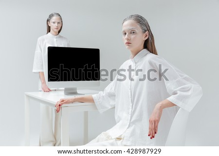 Two fashion mystical beautiful woman sitting beside table with computer, pc over gray background - stock photo