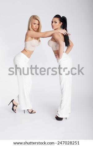 Two fashionable beautiful woman posing in studio. - stock photo