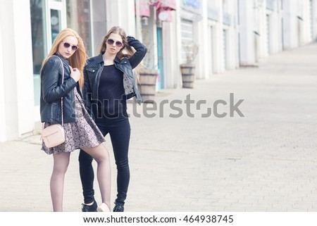 Two fashionable friends in outdoor shooting. Looking cool and posing
