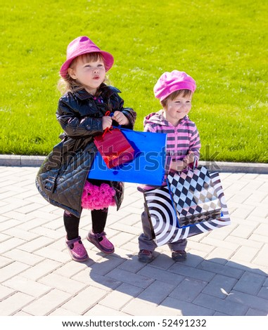 Two fashionable girls with lots of shopping bags - stock photo