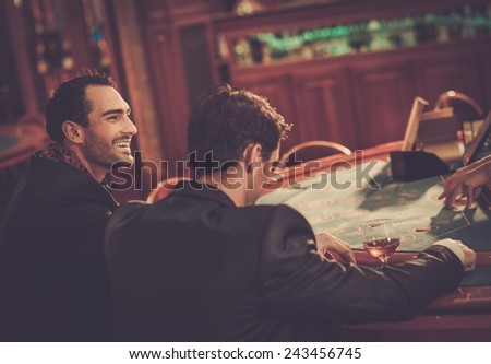 Two fashionable men in suits behind table in a casino - stock photo