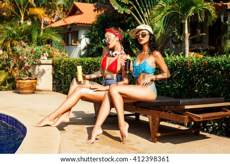 Two fashionable pretty cool hipster girls sunbathing by the pool, his feet smeared with cream for sunburn, bright sexy swimwear, shorts, cap, perfect tanned body, red lips, retro, Pin-up. - stock photo