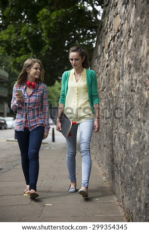 Two fashionable women walking down a city street, one with a skateboard.  - stock photo