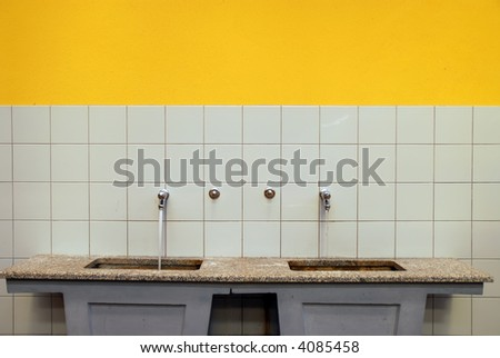 two faucets with running water in bathroom - stock photo