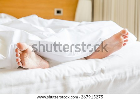 two feet in a bed - stock photo