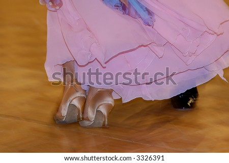 Two feet of woman dressed in lilac silky dress leaning against man's feet