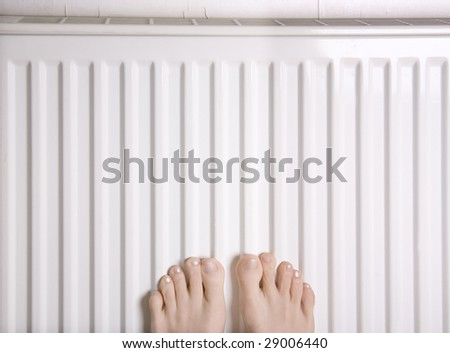 Two feet placed on a heater for warmth - stock photo