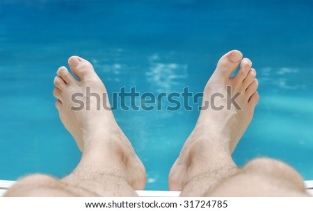 Two feet relaxing in sunlight with swimming pool water in the background. - stock photo