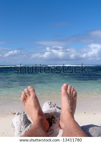 Two feet resting on a log on the beach