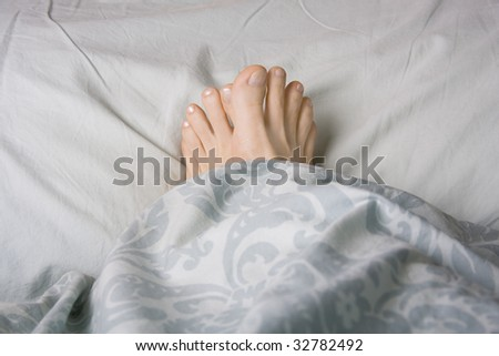 Two feet snuggled in a duvet for warmth,  shot landscape - stock photo