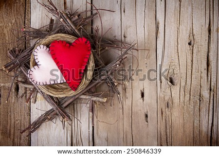 Two felt hearts in a rustic wooden nest on a wooden background - stock photo