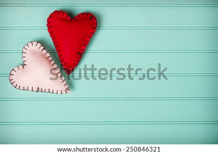 Two felt hearts on a retro turquoise background - stock photo