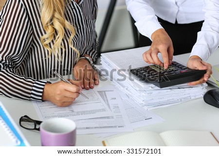 Two female accountants counting on calculator income for tax form completion hands closeup. Internal Revenue Service inspector checking financial document. Planning budget, audit concept - stock photo
