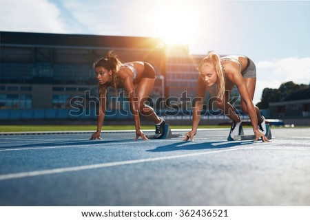 Two female athletes at starting position ready to start a race. Sprinters ready for race on racetrack with sun flare. - stock photo