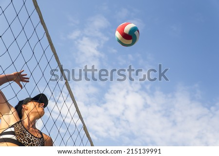 Two female athletes playing beach volleyball - stock photo