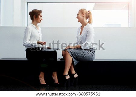 Two female business partners having pleasant conversation after working on touch pad while sitting in office interior, woman lawyer with digital tablet talking about something funny to her colleague - stock photo