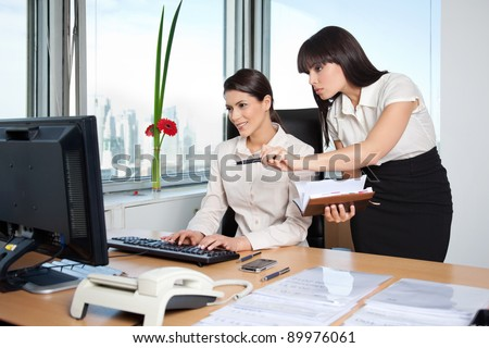 Two female business women in office setting working - stock photo